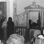 O Santo Padre Pio atende no confessionário.